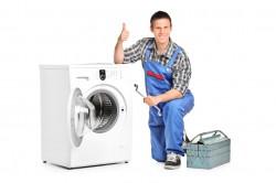 Repairman giving thumb up next to a washing machine
